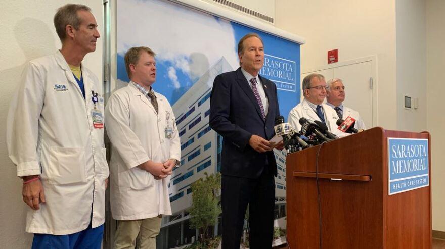 Man and doctors at podium