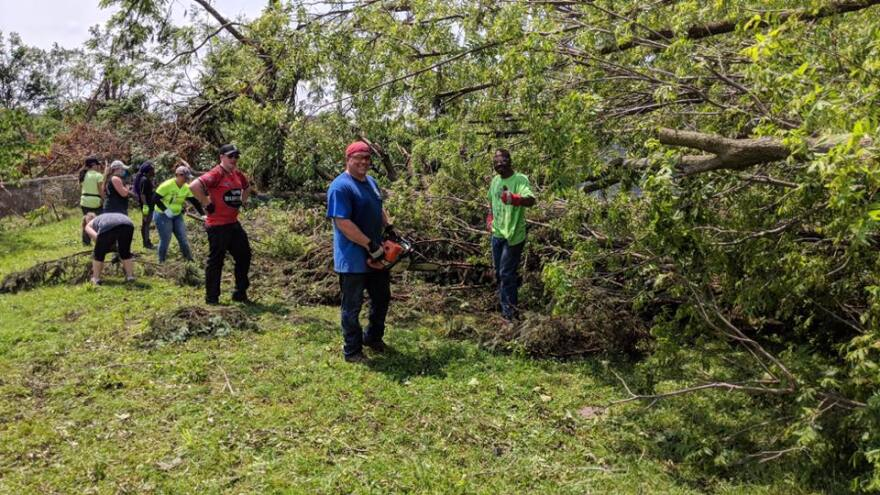 Volunteers use chainsaws to remove trees downed by the 2019 Memorial Day tornado.