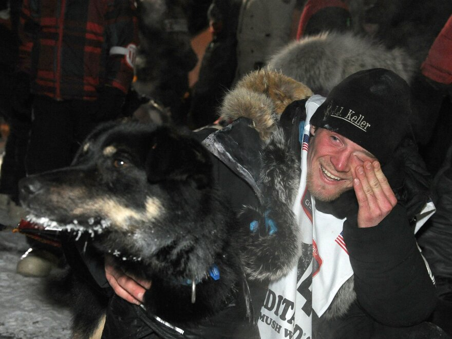 Dallas Seavey with his lead dog Beatle after crossing under the burled arch in Nome, Alaska, to win the 2014 Iditarod Trail Sled Dog Race on Tuesday.