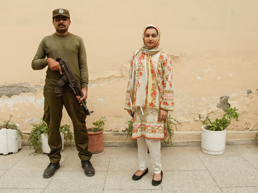 Khadija Saddiqi, 22, stands outside her family home with an armed guard who was assigned to protect her by the wife of the chief minister of Punjab. Saddiqi won a case against a classmate who tried to stab her to death in May last year after she ignored his advances.