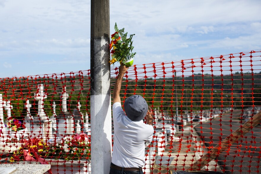 Francisco Rosado brought flowers for his mother's grave. But unable to reach it, he dropped them over the fence keeping him and other visitors away from damaged areas of the Lares Municipal Cemetery.