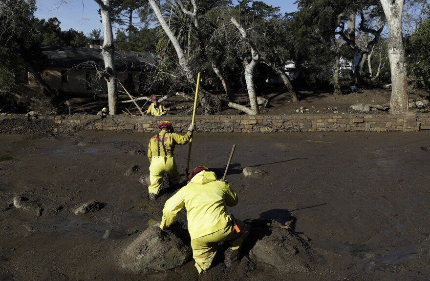 A Cal Fire search and rescue crew treads through mud near homes damaged by storms in Montecito, Calif., on Friday. Residents received advanced warnings of possible mudslides after recent wildfires had stripped hillsides of vegetation that normally holds soil in place, but unexpected heavy rains compounded the perilous conditions.