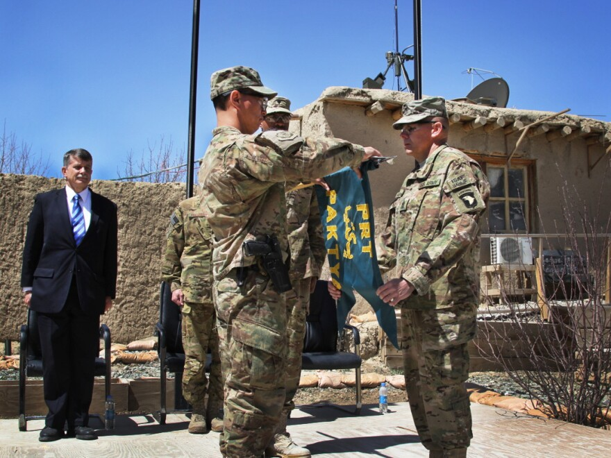 Lt. Col. John Chong (left), the last commander of the Paktia PRT, rolls up and cases the flag at the closing ceremony on April 9.
