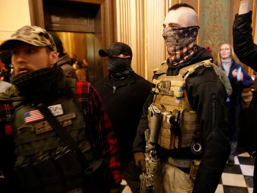 Protesters try to enter the chamber and are being kept out by police during a protest in Lansing, Mich., on Thursday.