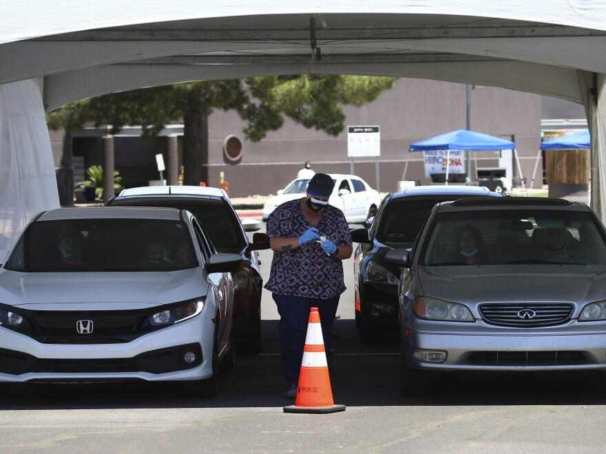 People get tested at a drive-through coronavirus testing site at South Mountain Community College on, July 9 in Phoenix.