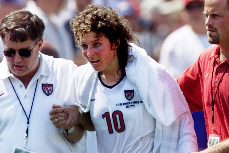 Michelle Akers, center, is helped off the field by the training staff after taking a hard hit in the second half of the Women's World Cup Final against China at the Rose Bowl in Pasadena, Calif., on July 10, 1999.