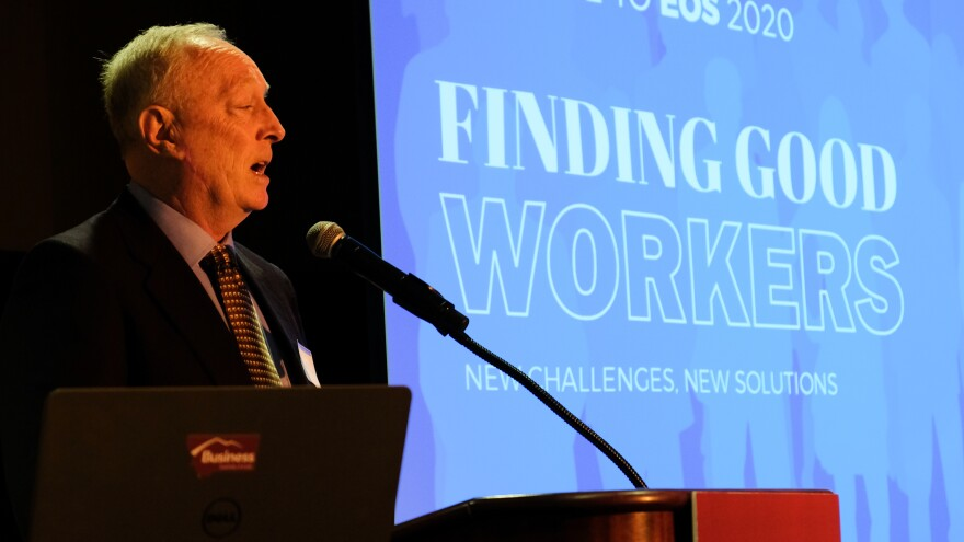 """John Hines stands in front of a podium and microphone against a blue screen that reads """"Finding Good Workers"""""""