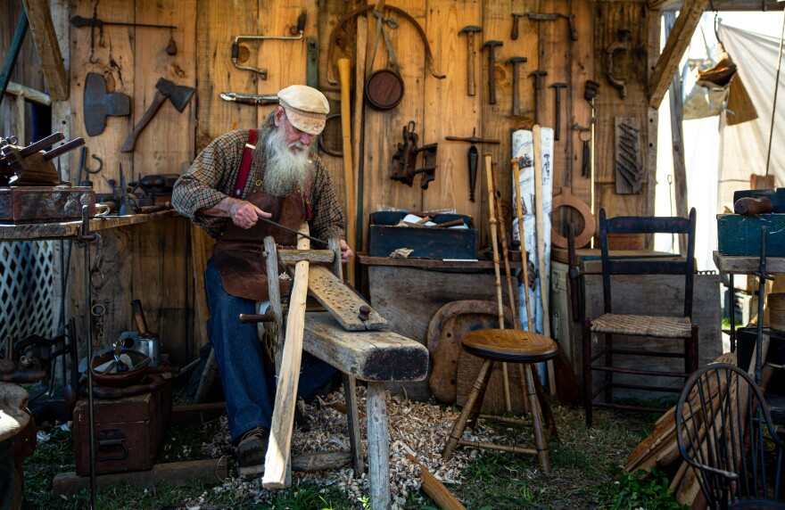 Albert Phillips sits in a workshop while demonstrating how to carve a piece of wood.