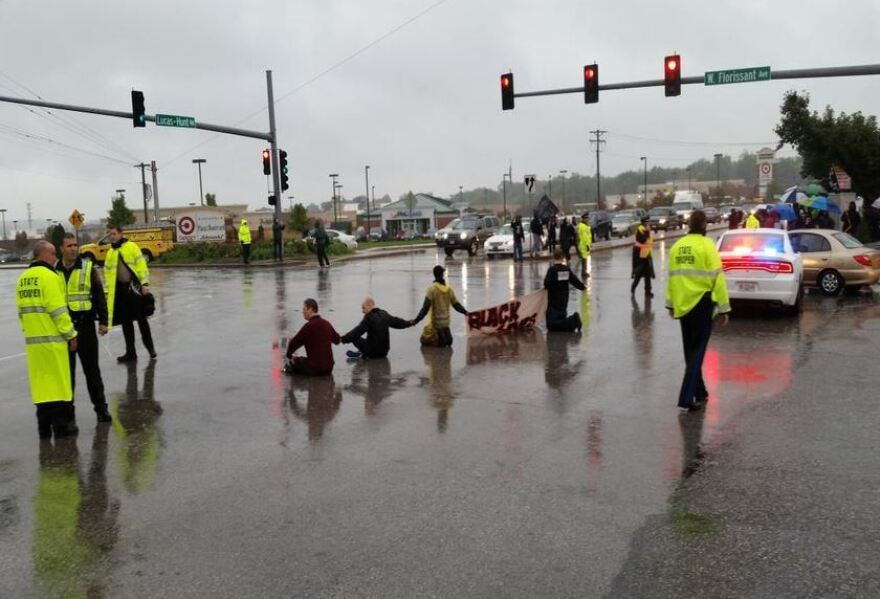 Demonstrators sit at the intersection of West Florissant and Lucas and Hunt, near the entrance of Emerson Electric. Police arrested six for blocking traffic.