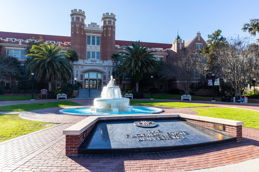 "Water flows out from a two-tiered fountain and into a large basin. In front of the fountain is a large black plaque that reads, ""The Florida State University."" Behind the fountain is a brick building."