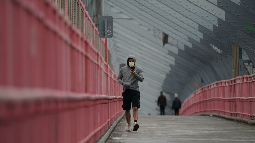 A pedestrian in a face mask crosses the Williamsburg Bridge in New York City last month. U.S. health authorities have announced they're changing the official recommendations on face masks, now urging people to wear them in public spaces to help slow the spread of the coronavirus.