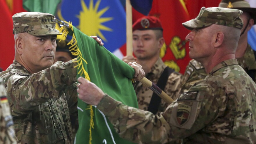 U.S. Gen. John Campbell (left) and Command Sgt. Maj. Delbert Byers open the Operation Resolute Support flag during a ceremony at the International Security Assistance Force headquarters in Kabul, Afghanistan on Sunday.