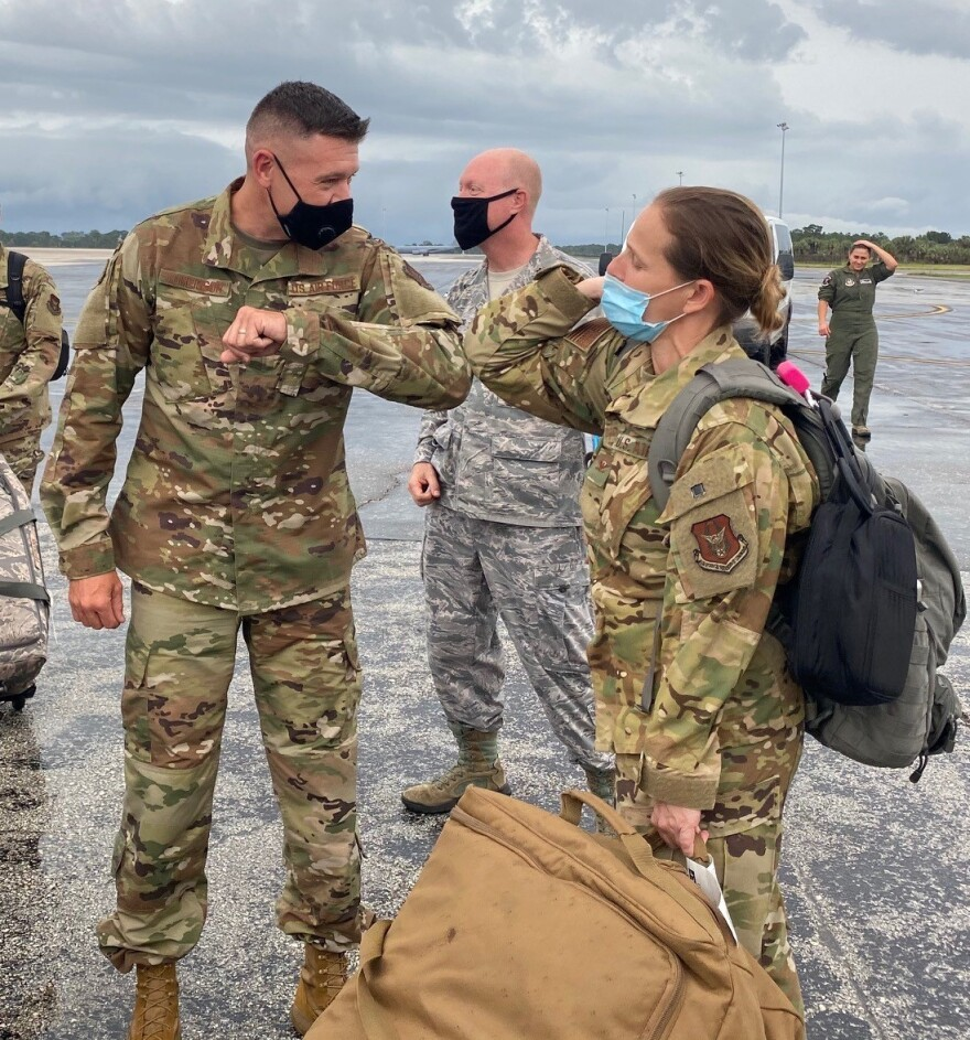 Chief Master Sgt. Paul Tomlinson, 927th Command Chief, and Col. Jennifer Robyn Ratcliff, 927th Aerospace Medicine Squadron Commander, greet each other with an elbow bump as she and the 927th team returned to MacDill AFB.