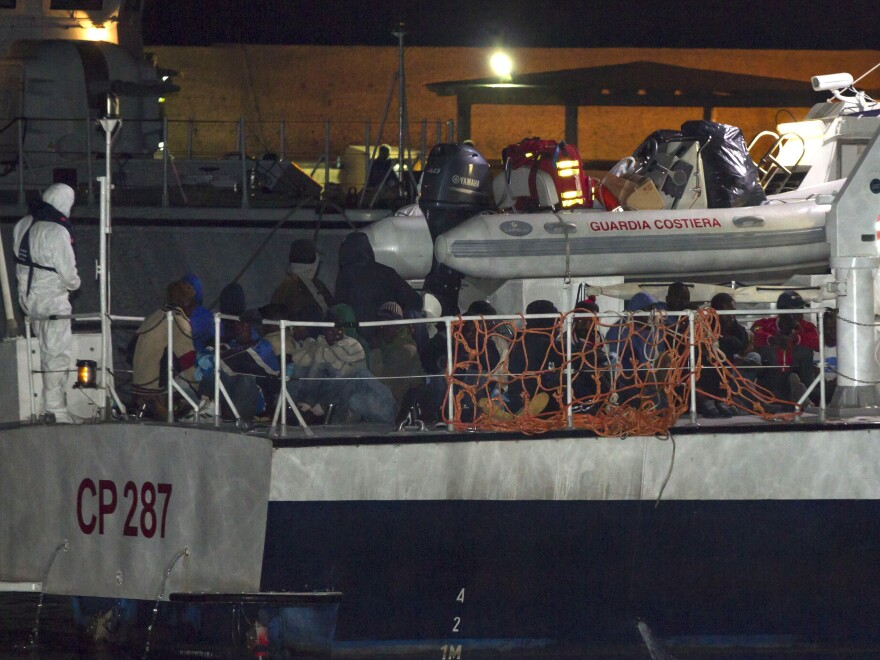 Migrants arriving at the Lampedusa island harbor aboard an Italian Coast Guard ship early Sunday. Ships rescued 3,690 migrants in just one day from smugglers' boats on the Mediterranean Sea off the Libyan coast, the Italian Coast Guard says.