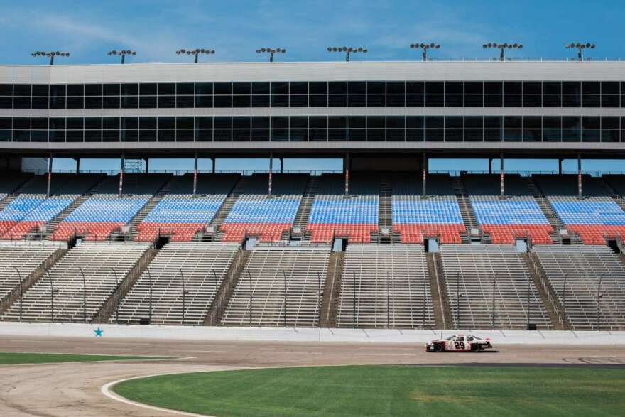 race car drives past empty stands