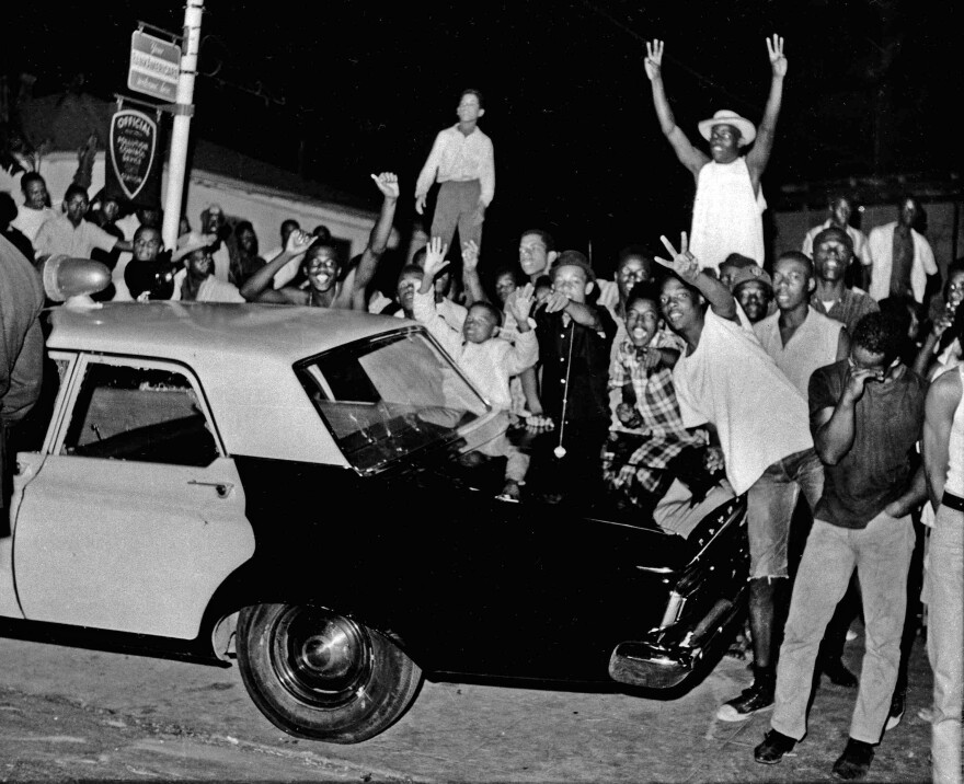 Demonstrators push against a police car in the Watts district of Los Angeles on Aug. 12, 1965. The Watts riots raged for most of a week. When the smoke cleared, 34 people were dead, more than 1,000 were injured and hundreds of buildings were destroyed.