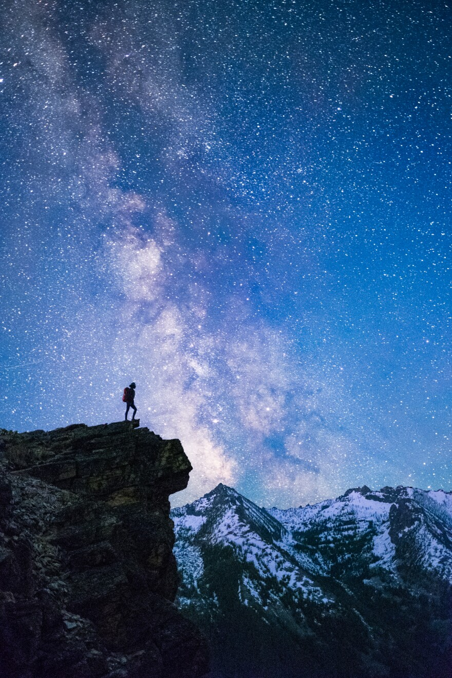 A person stands backlit by the Milky Way