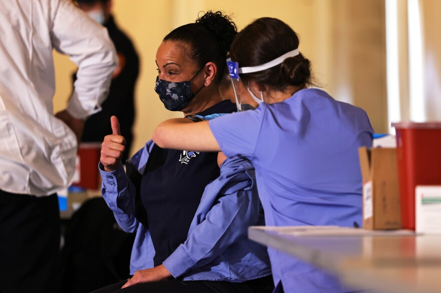 A member of FDNY EMS gives a thumbs up while receiving Moderna's coronavirus vaccine in late December. By mid-January, New York City Medical Reserve Corps volunteers also were mobilized to help with the vaccine effort.