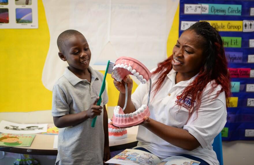 Dana Pittman, 5, helps brush the giant teeth in Willona Milton's classroom at Morton Clark Head Start in Bradenton.