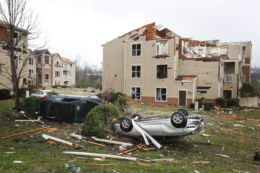Two cars are turned over in front of a damaged apartment complex, on Tuesday in Jacksonville, Ala. A violent storm, including several tornadoes, erupted in a multi-state swath from Tennessee to Florida late Monday.