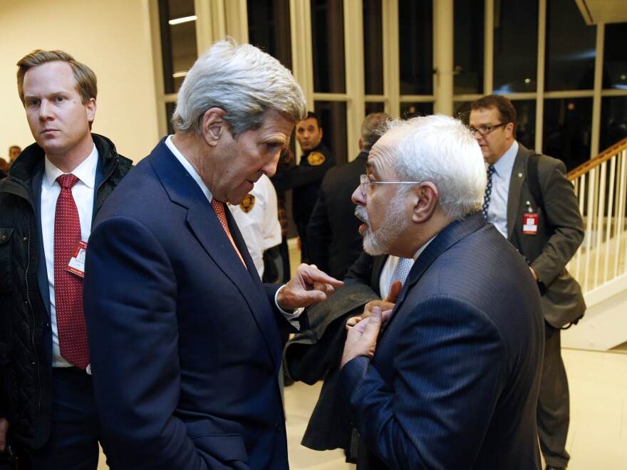 U.S. Secretary of State John Kerry (left) speaks with Iranian Foreign Minister Mohammad Javad Zarif after the IAEA verified that Iran has met all conditions under the nuclear deal.
