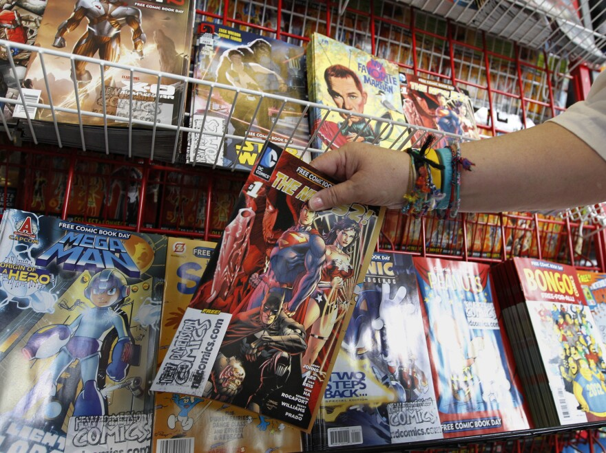 Mary Ann Shilts takes one of the give away comic books from the display rack at the New Dimensions Comics store in Cranberry, Pa., Butler County, as part of Free Comic Book Day 2012. Free Comic Book Day 2013 is Saturday, May 4.