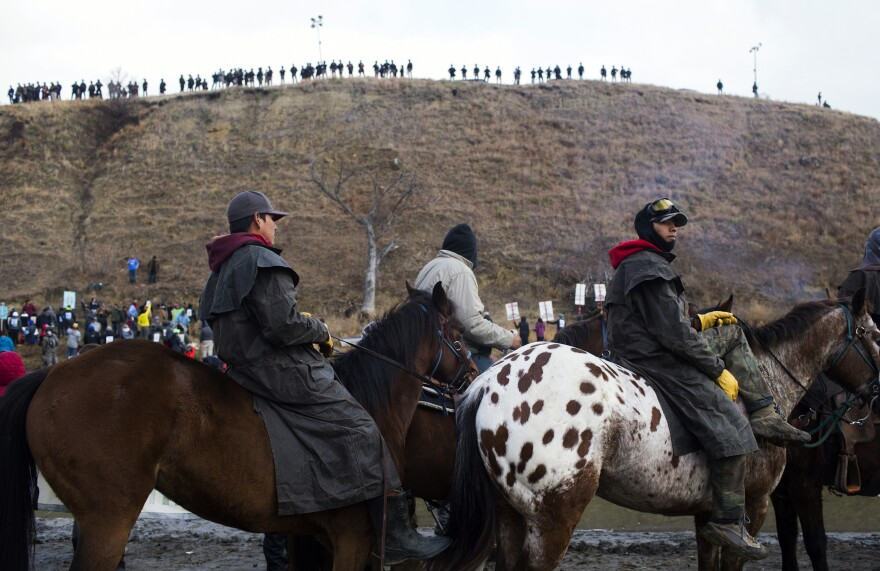 Protesters gather at Standing Rock Reservation on Thanksgiving Day to build a bridge to Turtle Island, which they consider sacred ground. Police are seen lining the island hill beyond them.