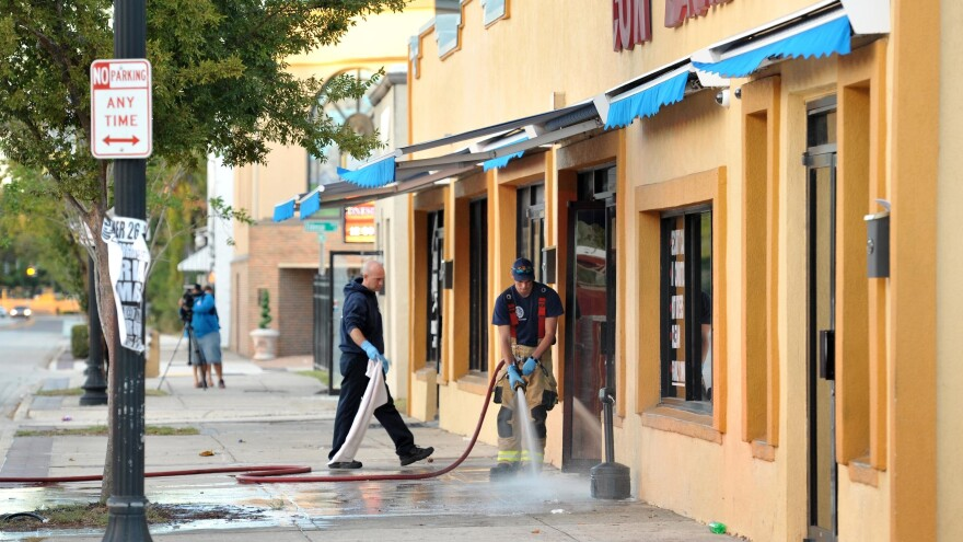 JFRD personnel use chemicals and hoses to clean up the blood outside the Maytag Coin Laundry on A. Philip Randolph Blvd. in Jacksonville after a drive by shooting.