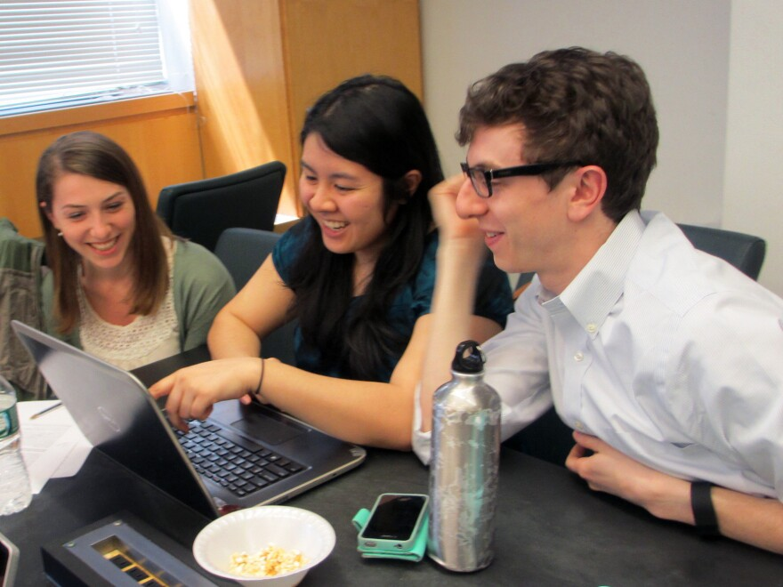 (Left to right) Students Christine Schindler, Mary Quien and Micah Timen share popcorn and a laugh during a research session. Timen worked as an accountant before medical school; his database project tracked the relative costs of a hip replacement throughout New York compared to the relative costs of a fast-food hamburger.
