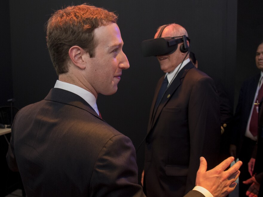 Facebook founder and CEO Mark Zuckerberg looks on a Peruvian President Pedro Pablo Kuczynski demos a virtual reality headset.