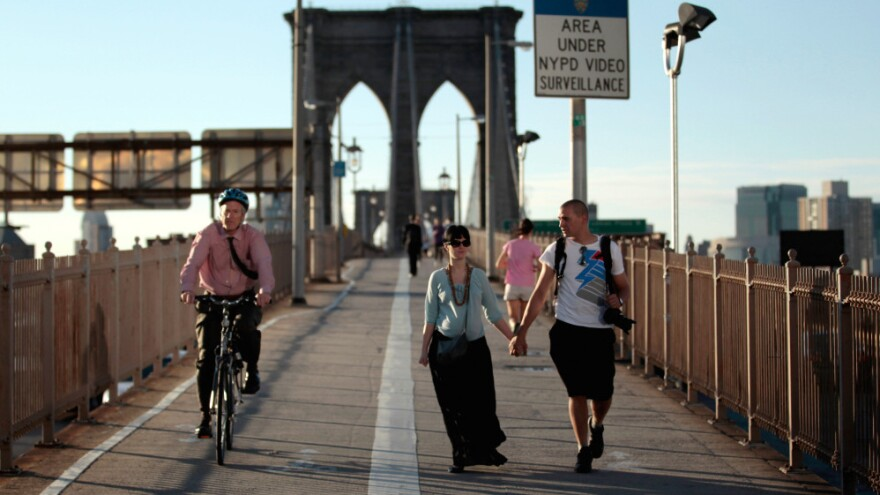 Americans walk less than the citizens of any other industrialized nation, says Tom Vanderbilt. In this file photo from last summer, pedestrians and a cyclist cross the Brooklyn Bridge in New York City.