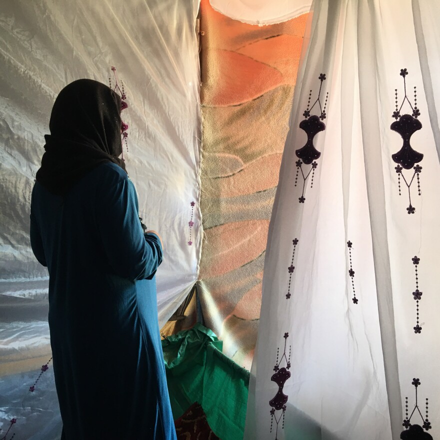Ftaim al-Saleh stands in the tent donated by friends and relatives after her four youngest children died when their tent caught fire, as she and her husband were working in the fields. The Syrian refugee couple came to Jordan eight years ago, after airstrikes destroyed their house.