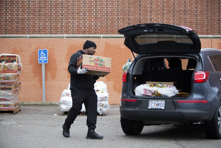 A staff member loads up food donations for a church group at an emergency food distribution center set up outside Better Family Life on Thursday, March 26, 2020.