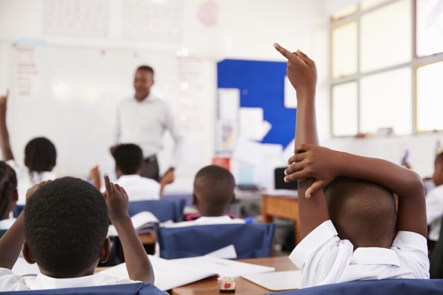 Kids raising hands to answer teacher at an elementary school lesson