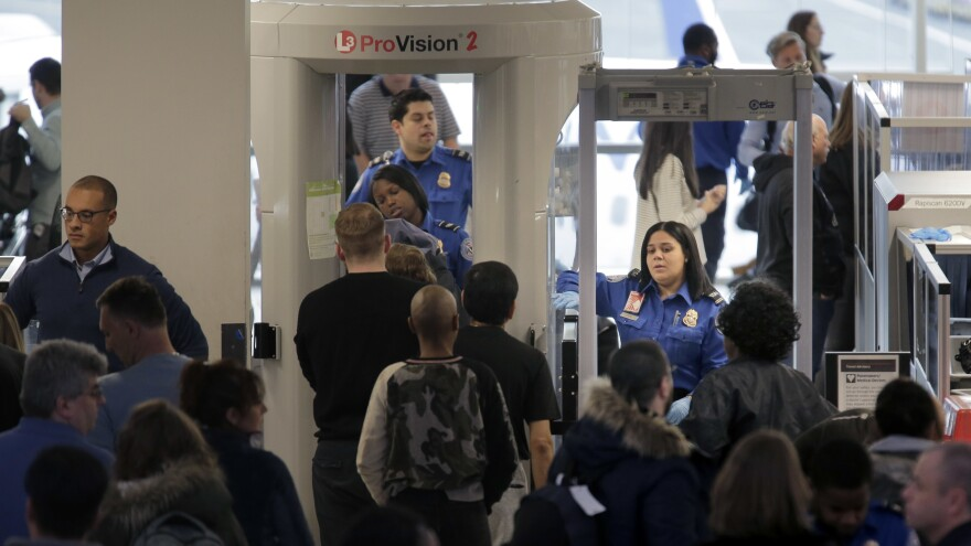 Transportation Security Administration agents help passengers through a security checkpoint at Newark Liberty International Airport in Newark, N.J., on Monday. Agents have been working without pay since the shutdown began.