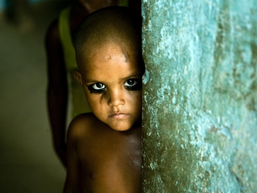 A child wearing the traditional eyeliner kajal peeps from behind a door in Allahabad, India.