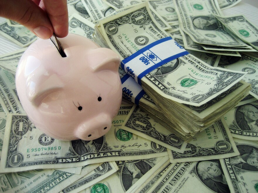 Photo illustration showing a piggy bank and dollar bills