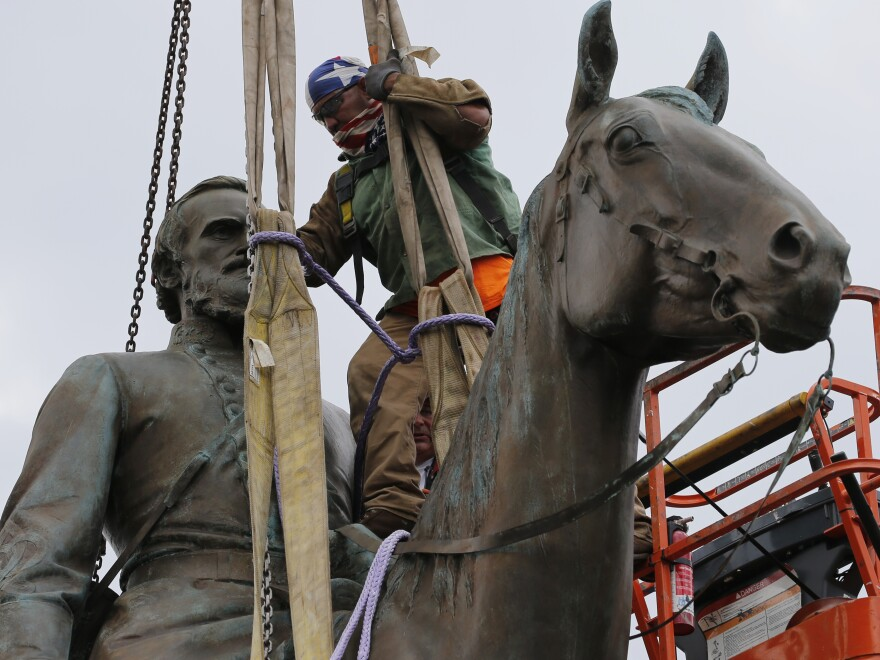 Work crews remove the statue of Confederate Gen. Stonewall Jackson on Wednesday in Richmond, Va. The city's mayor, Levar Stoney, has ordered the immediate removal of multiple Confederate statues in the city, saying he was using his emergency powers to speed up their removal for public safety.