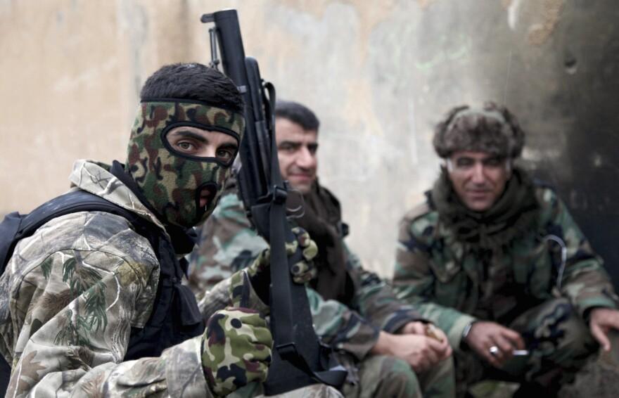 Kurdish peshmerga fighters rest on the outskirts of Mosul on Jan. 30.
