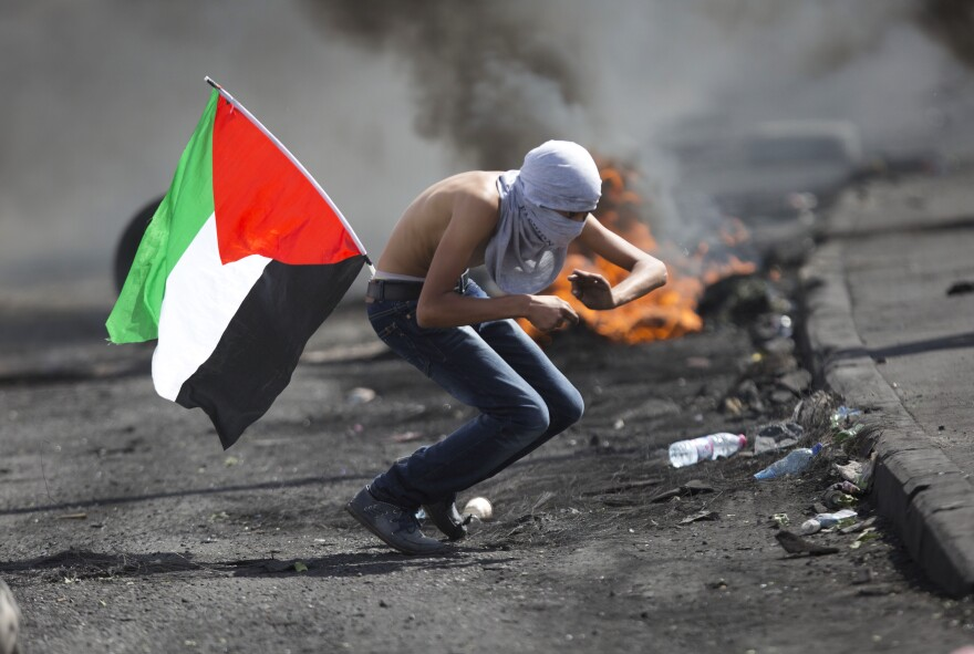 A Palestinian tries to dodge rubber coated bullets during clashes with Israeli troops near Ramallah, West Bank, on Tuesday.
