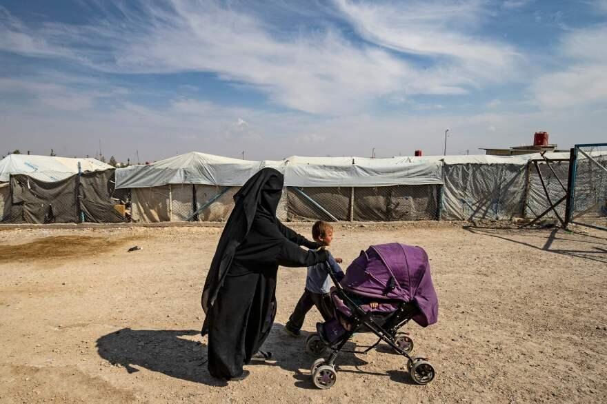 A woman walks with children at the Kurdish-run al-Hol camp where families of ISIS foreign fighters are held in northeastern Syria earlier this month.