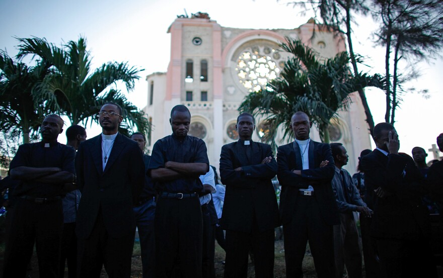 Men stand in front of the destroyed cathedral in Port-au-Prince and listen to the archbishop's funeral service.