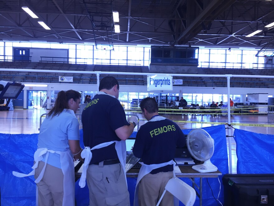 Forensic scientists prepare their fingerprinting station for a mock morgue identification exercise in a gymnasium at Miami-Dade College's North Campus on Wednesday.