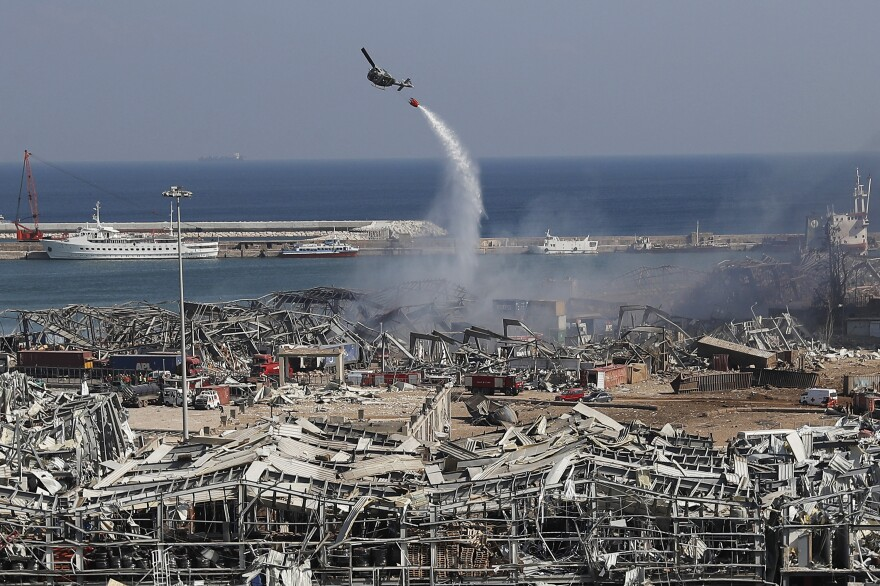An army helicopter drops water at the scene of Tuesday's massive explosion that hit the seaport of Beirut on Wednesday. Residents of Beirut awoke to a scene of utter devastation on Wednesday, a day after a massive explosion sent shock waves across the Lebanese capital, killing dozens of people and wounding thousands.