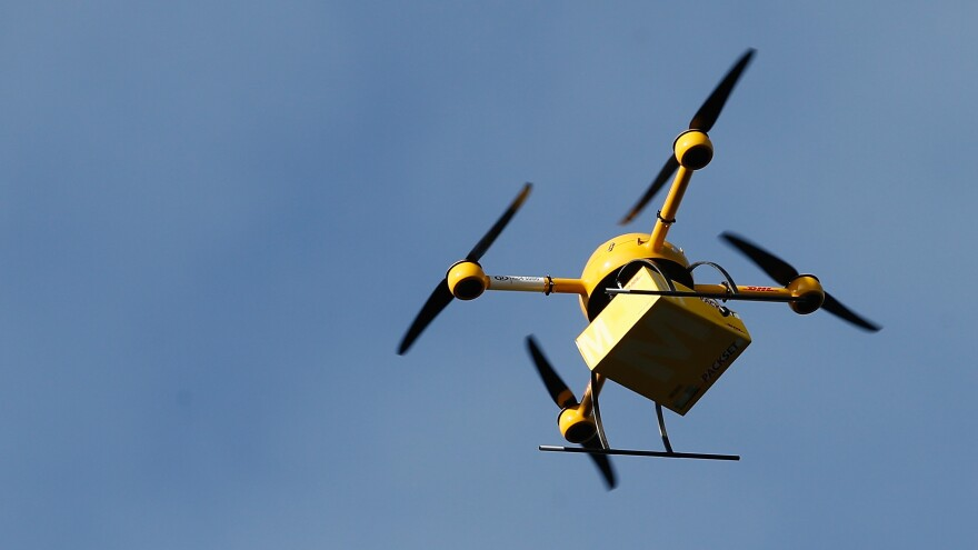 It's a drone delivery! This copter is ferrying medicine from a pharmacy to the headquarters of Deutsche Post in Bonn, Germany, part of a test of drone capabilities.