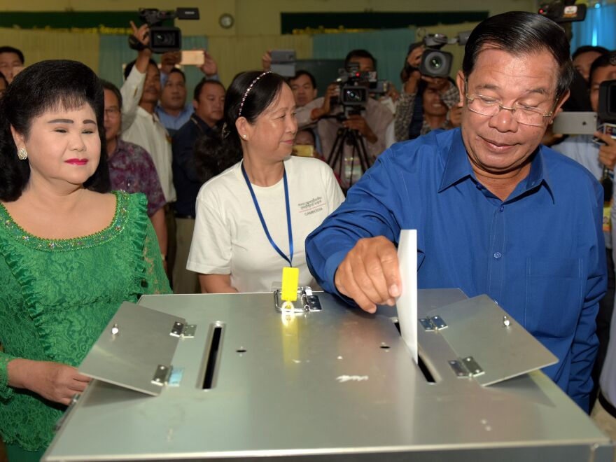 Cambodian Prime Minister Hun Sen cast his ballot as his wife Bun Rany (L) looks on at a polling station in Kandal province on June 4, 2017.