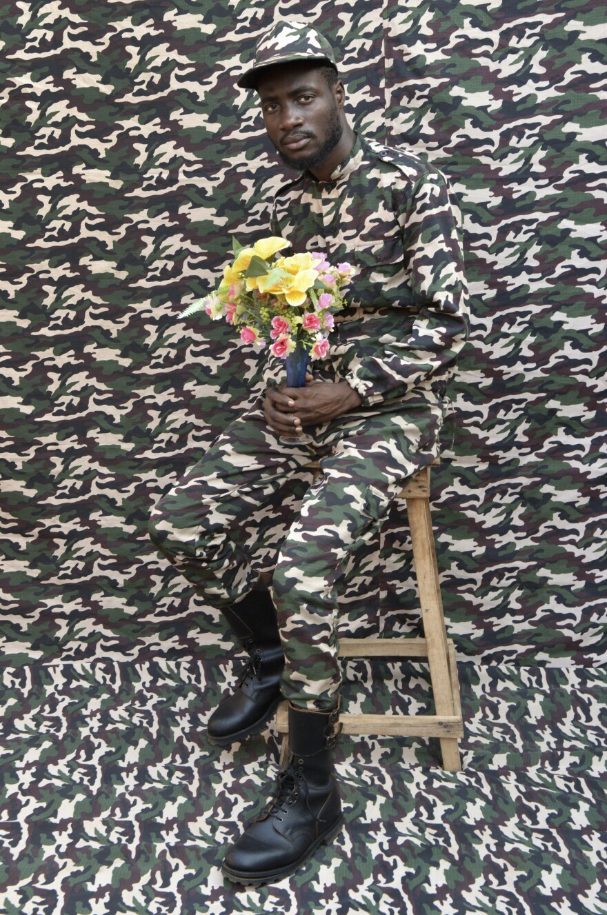 "Born in 1965 in Porto Novo, Benin, Leonce Raphael Agbodjelelou <em>""</em>draws inspiration from growing up working in his father Joseph's prestigious studio and casts models in place of paying clientele,"" says Yossi Milo, who curated the exhibit. Here, military camouflage pattern seems to merge subject and backdrop into one even while colorful flowers burst out of the background."
