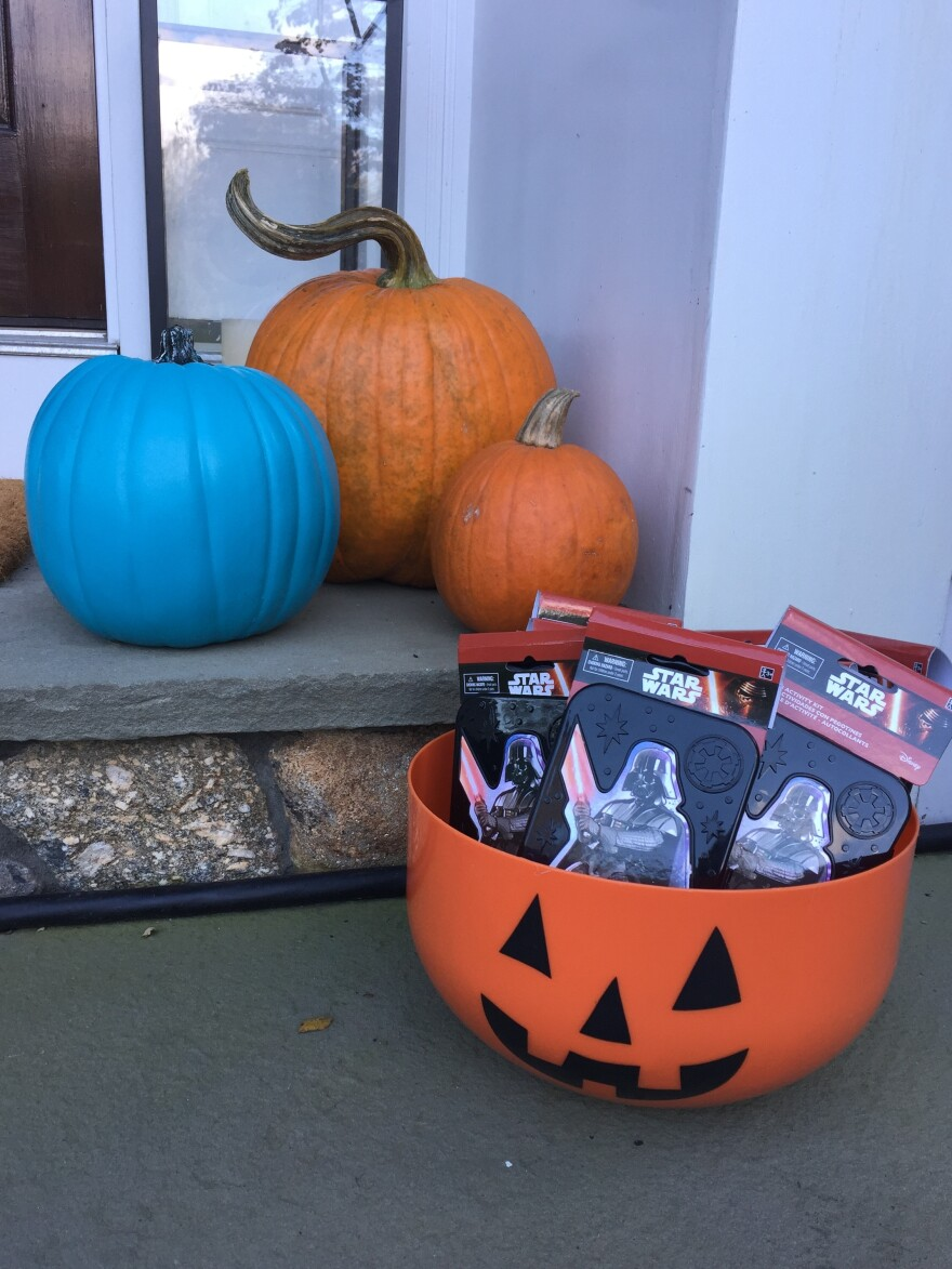 Hillary Carter displays a teal pumpkin on her front step along with a bowlful of toys that kids with food allergies can choose instead of candy.