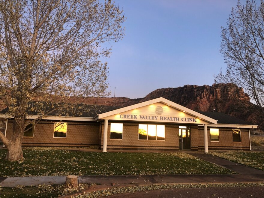 A one-story, ranch style building sits in front of a backdrop of red cliffs at dusk.