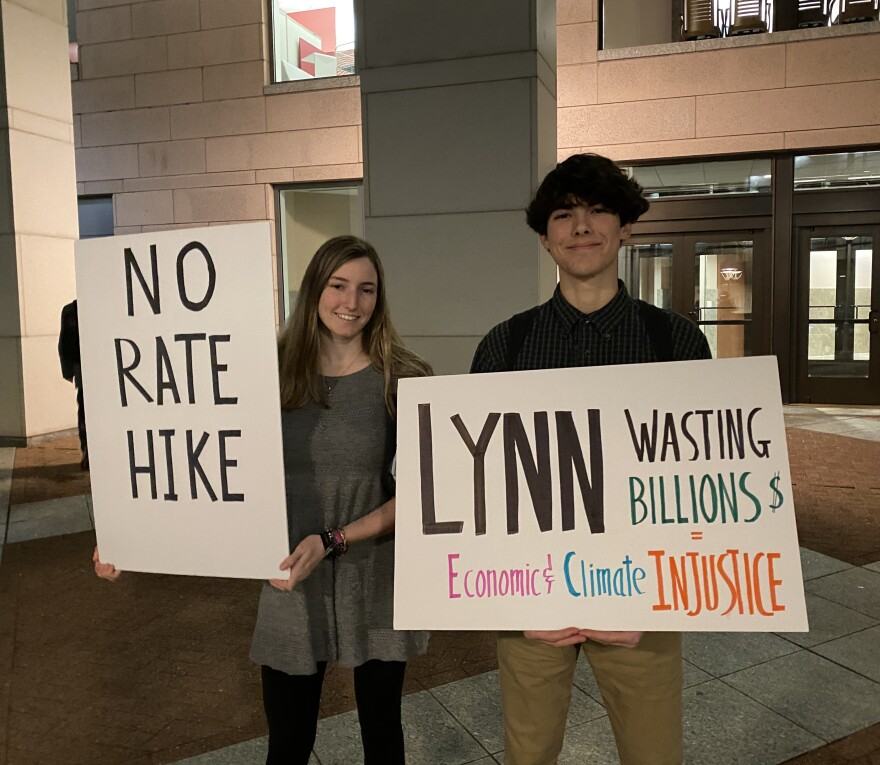 Kate Lewin and Lucas Blanco protest Duke Energy outside the Mecklenburg County Courthouse ahead of the company's rate increase public hearing.